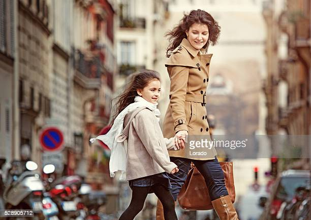 Brunette mother daughter walking in Paris streets on spring afternoon