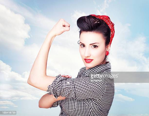 Brunette striking a famous Rosie Riveter pose
