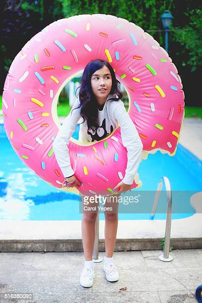 brunette teen holding PINK donuts inflatable ring.Poolside