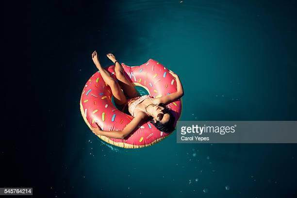 brunette teen in donuts inflatable ring.