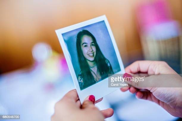 brunette teenager holding a polaroid picture