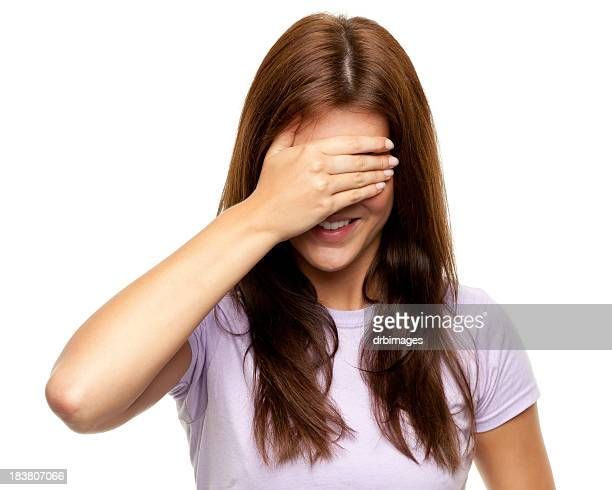 Brunette woman covering eyes with hand