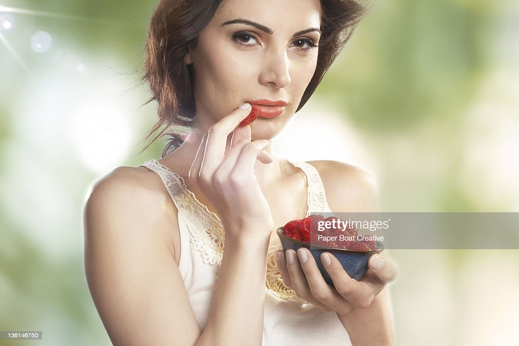 brunette woman eating a bowl of raspberries : Stock Photo