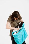 Brunette woman looking into a full handbag