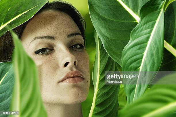 Brunette woman surrounded by green leaves