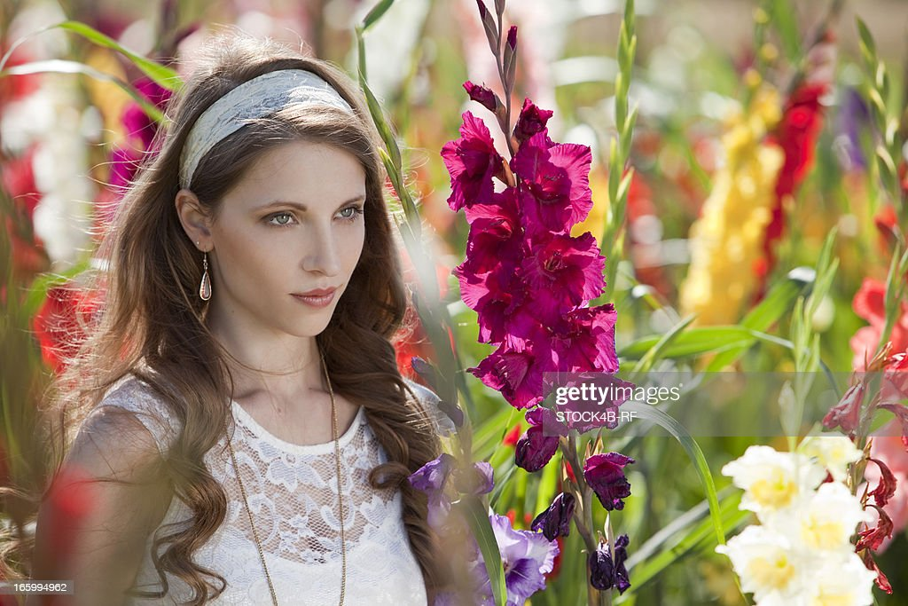 Brunette young woman surrounded by flowers : Stock Photo