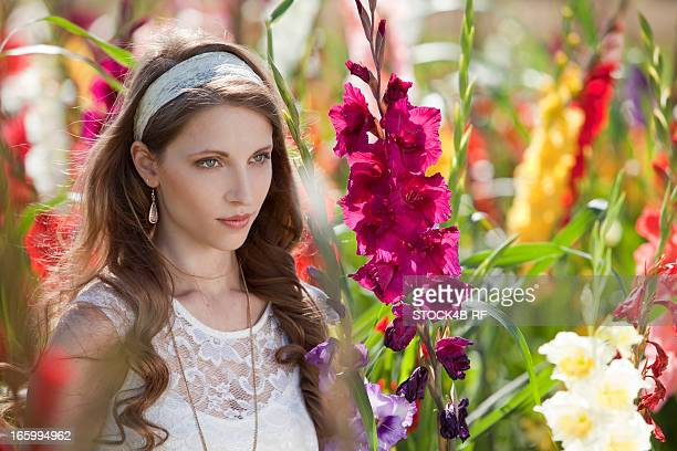 Brunette young woman surrounded by flowers