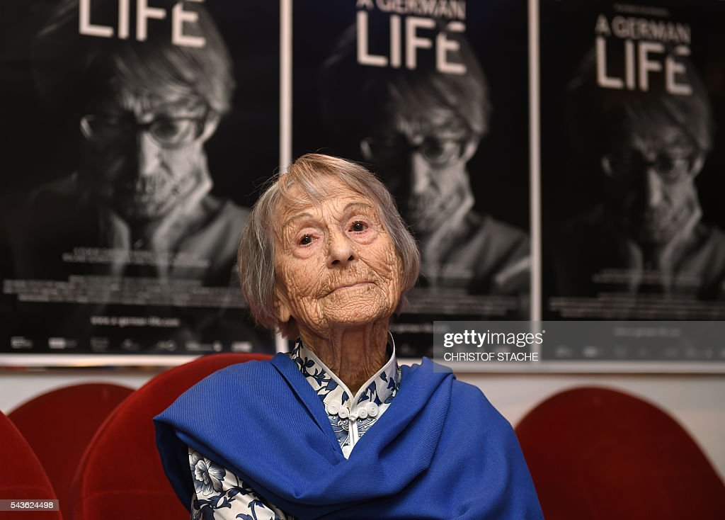 Brunhilde Pomsel, former secretary of Nazi propaganda chief Joseph Goebbels, sits on a cinema chair in front of posters for the movie 'A German life' in a cinema in Munich, southern Germany, on June 29, 2016. / AFP / CHRISTOF