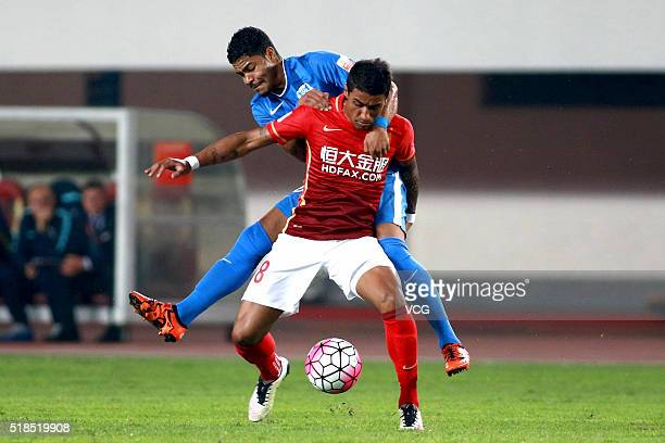 Bruninho of Guangzhou RF competes for the ball with Paulinho of Guangzhou Evergrande during the round three match of CSL Chinese Football Association...