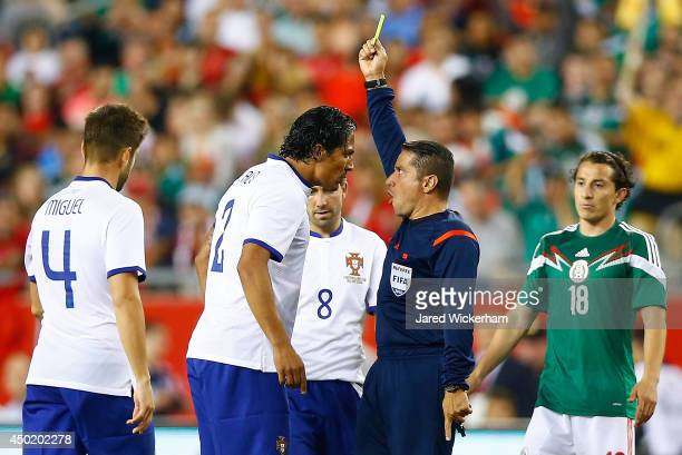 Bruno Alves of Portugal is given a yellow card by referee Jeffrey Solis in the second half against Mexico during the international friendly match at...