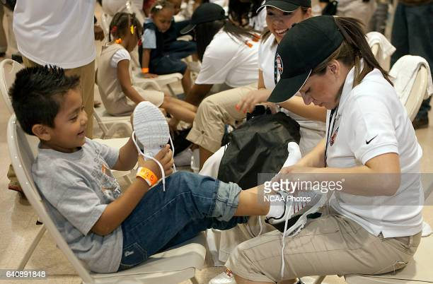 Bruno Amborsio takes a look at his new sneakers as he is fitted by volunteer Cindy Rubio right and Kimberly Lopez center looks on at the Final Four...