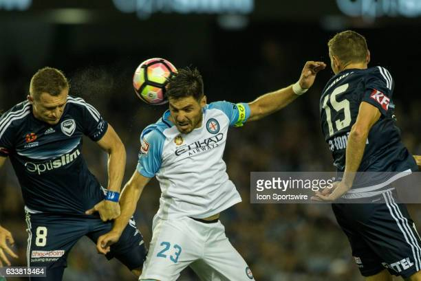 Bruno Fornaroli of Melbourne City heads the ball in a contest with Besart Berisha of Melbourne Victory and Alan Baro of Melbourne Victory during the...