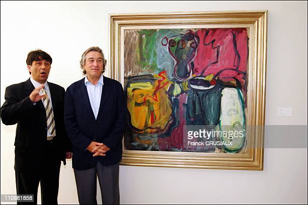 Bruno Gaudichon curator of La Piscine and US actor Robert De Niro pose next to a painting by his father Robert Sr which was donated to La Pisine by...