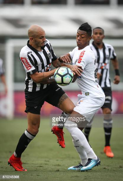 Bruno Henrique of Santos battles for the ball with Fabio Santos of Atletico Mineiro during the match between Santos and Atletico Mineiro as a part of...