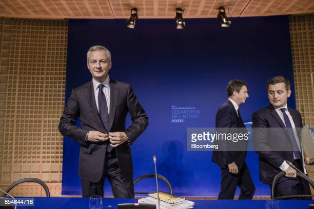 Bruno Le Maire France's finance minister buttons his jacket as Benjamin Griveaux France's junior economy minister second right and Gerald Darmanin...