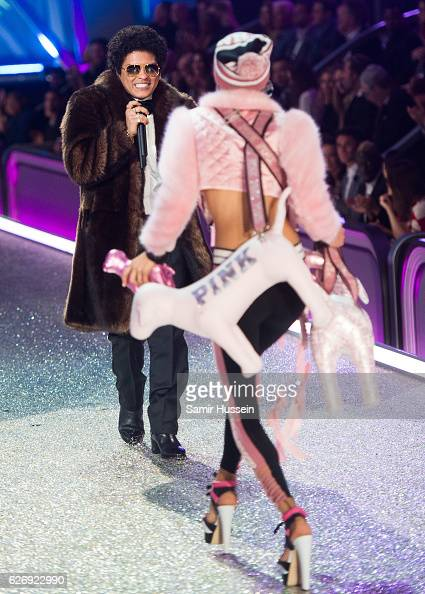 Bruno Mars performs as Dilone walks the catwalk during the annual Victoria's Secret fashion show at Grand Palais on November 30 2016 in Paris France