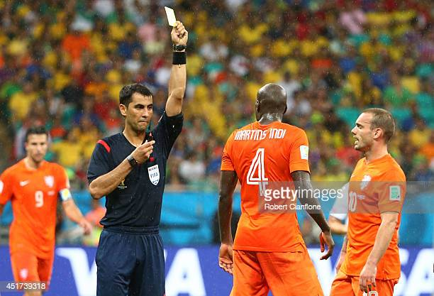 Bruno Martins Indi of the Netherlands is shown a yellow card by referee Ravshan Irmatov during the 2014 FIFA World Cup Brazil Quarter Final match...