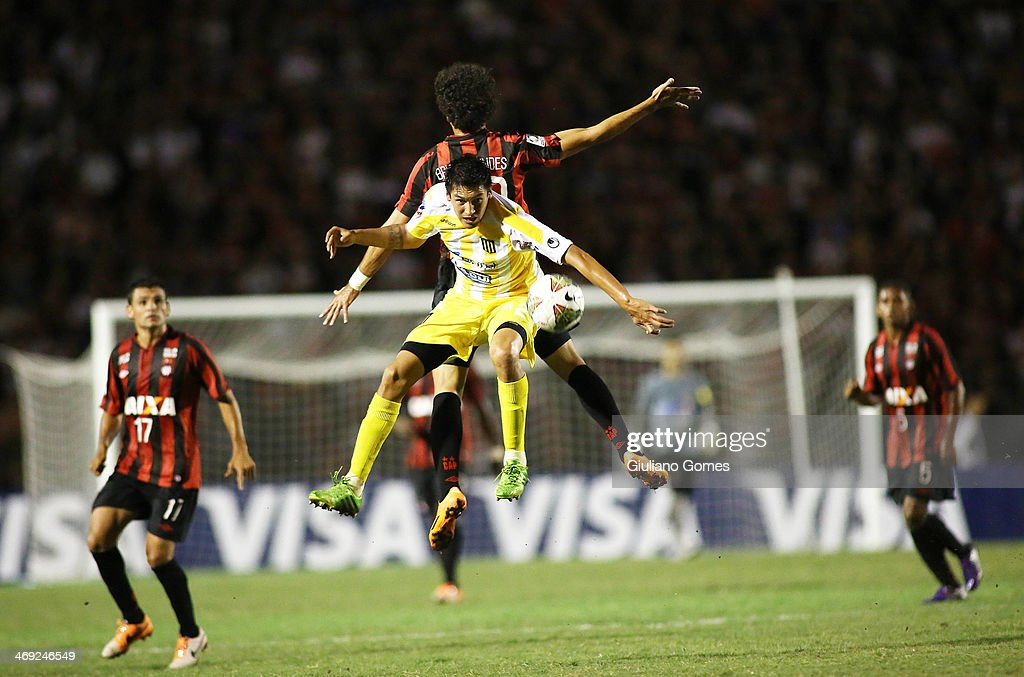 Bruno Mendes of Atletico Paranaense battles for the ball against Marcos Barrera of The Strongest during a match between Atletico Paranaense and The Strongest as part of Copa Bridgestone Libertadores 2014 at Durival Britto Stadium on February 13, 2014 in Curitiba, Parana, Brazil.