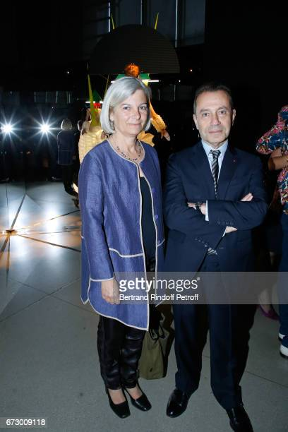 Bruno Racineand his wife pose in front the works of JeanPaul Goude during the 'Societe des Amis du Musee d'Art Moderne du Centre Pompidou' Dinner...