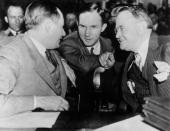 Bruno Richard Hauptmann later convicted of kidnapping and murdering Charles Lindbergh Jr confers with his lawyers Lloyd Fisher and Frederick Pope...