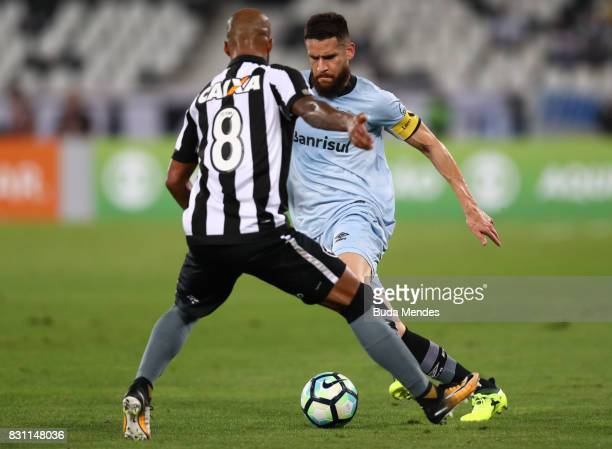 Bruno Silva of Botafogo struggles for the ball with Marcelo Oliveira of Gremio during a match between Botafogo and Gremio as part of Brasileirao...