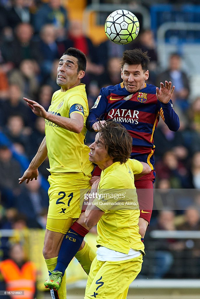 Bruno Soriano (21) and Tomas Pina (4) of Villarreal competes for the ball with Lionel Messi of Barcelona during the La Liga match between Villarreal CF and FC Barcelona at El Madrigal on March 20, 2016 in Villarreal, Spain.