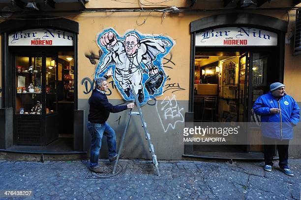 Bruno the owner of the bar Nilo finish to attach on the wall a street art mural showing Pope Francis as a superman flying through the air with his...