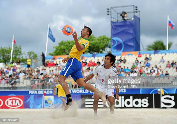 Bruno Xavier of Brazil controls the ball as Teruki Tabata of Japan looks on during the FIFA Beach Soccer World Cup Tahiti 2013 Quarter Final match...