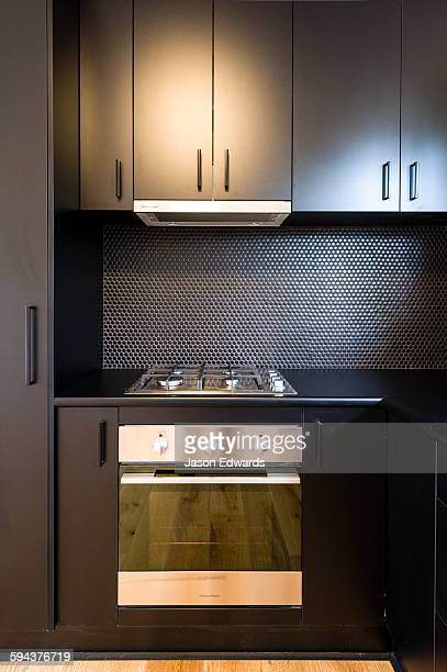 A black modern oven and range cooker in a kitchen in an inner city apartment.