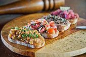 Bruschetta served on a french baguette with eggplant paste, tomatoes, chicken paste and minced raw tuna