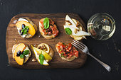 Bruschetta set with glass of white wine. Black plywood background, top view, horizontal composition