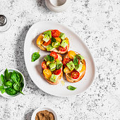 Bruschetta with cherry tomatoes, avocado and basil. On a light background. Healthy snack