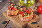 Italian bruschetta with chopped tomatoes, basil, herbs and olive oil on grilled crusty bread. Italian cuisine  concept.