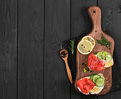 Bruschetta with salmon and fresh cucumber on cutting board on black wooden background. Top view.