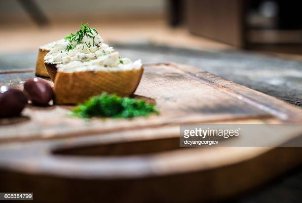 Bruschetta with soft cream cheese and olives on chopping board