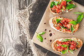 Bruschetta with tomatoes and basil on the wooden board top view horizontal