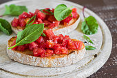 bruschetta with tomatoes and fresh spinach on a light wooden background