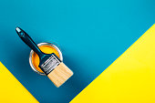 Brush on open can of yellow color paint on yellow and blue background. Flat lay style. Renovation concept.