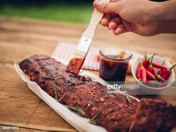 Brush painting barbecue sauce onto a rack of ribs