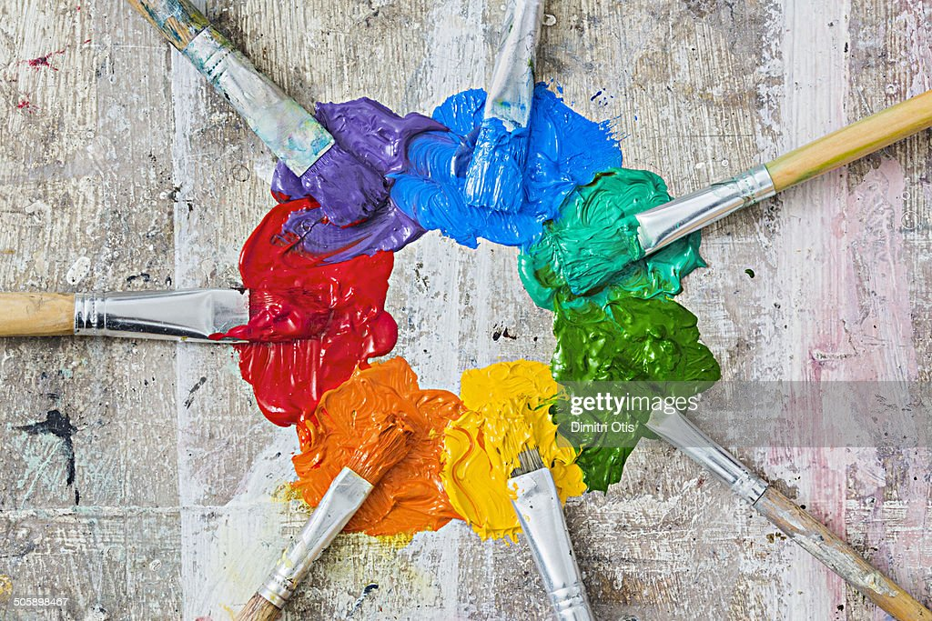 Brushes and oil paint forming a messy colour wheel