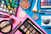Brushes with an eyeshadow palette and lipstick in pink and blue geometric background