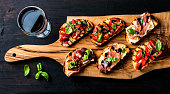 Brushetta set for wine. Variety of small sandwiches with prosciutto, tomatoes, parmesan cheese, fresh basil and balsamic creme served with glass of red wine on rustic wooden board over dark background