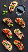 Brushetta set with glass of red wine. Variety of small sandwiches with prosciutto, tomatoes, cheese, herbs and balsamic creme on dark wooden background, top view