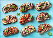 Brushetta snacks for wine. Variety of small sandwiches on turquoise blue backdrop, top view
