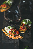 Wine and snack set. Brushetta with roasted eggplant, tomatoes, garlic, cream cheese, arugula and glass of red wine on wooden board over dark background, selective focus. Slow food, party food concept
