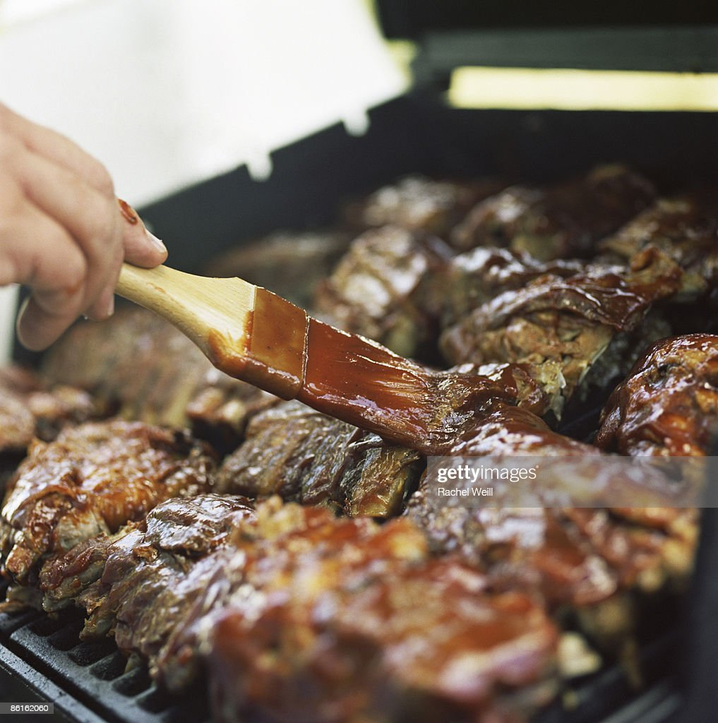 Brushing BBQ sauce on meat : Stock Photo