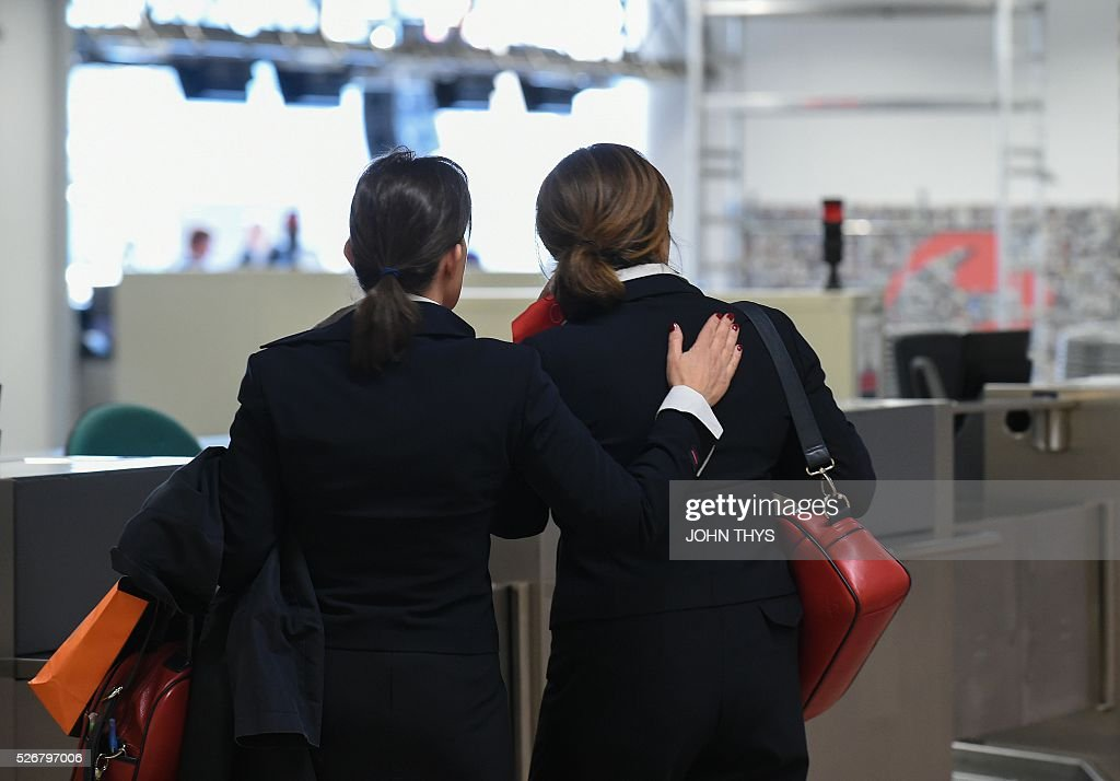 Brussels Airlines employees react at the site of attacks during the partial reopening of the departure hall of Brussels Airport in Zaventem on May 1, 2016, after it was badly damaged in twin suicide attacks on March 22, that killed 16 people. A total of 32 people were killed and more than 300 wounded in coordinated suicide bombings at the airport and a metro station in central Brussels on March 22 in Belgium's worst ever terror attacks. / AFP / JOHN