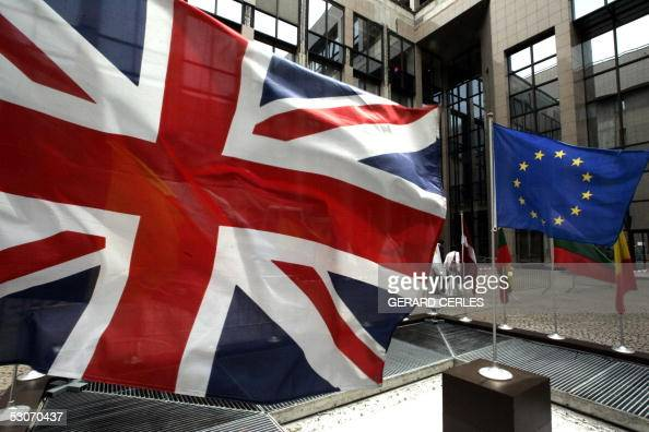A European Flag and the Union Jack hang in front of the Justus Lipsius the European Union's headquarters building in Brussels 15 June 2005 on the eve...