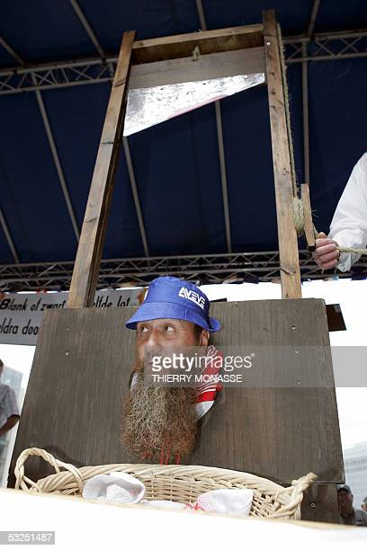 A man rest his head in a guillotine to protest against the future of beet producers in the European Union at Brussels 18 July 2005 Thousands of...