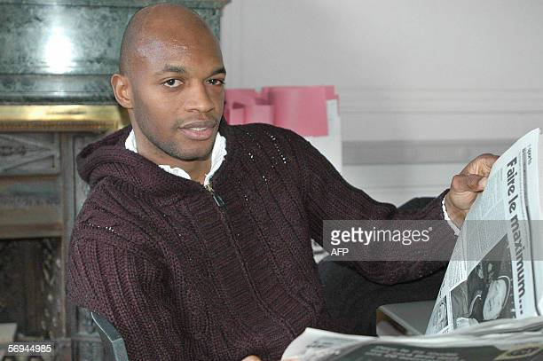 Roeselare's French soccer player Wagneau Eloi holds a newspaper after making a press announcement 26 February 2006 in Brussels to deny accusations...